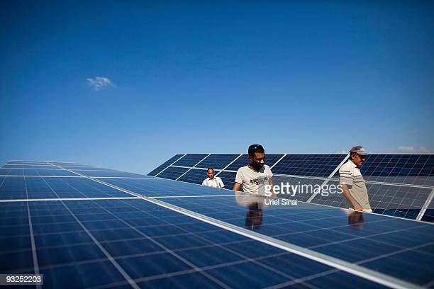 Workers install photovoltaic solar panels to create electricity from the sun on the roof of a chicken coop November 15 2009 in the village of Ein...
