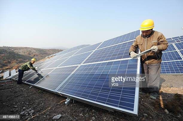 Workers install polycrystalline silicon solar panels as terrestrial photovoltaic power project starts in Guanshui Town of Muping District on November...