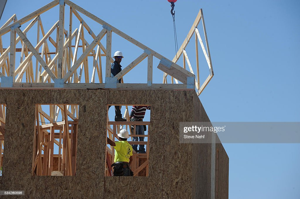 Workers install roof trusses on a home under construction in the Copperleaf development Wednesday morning, May 25, 2016.