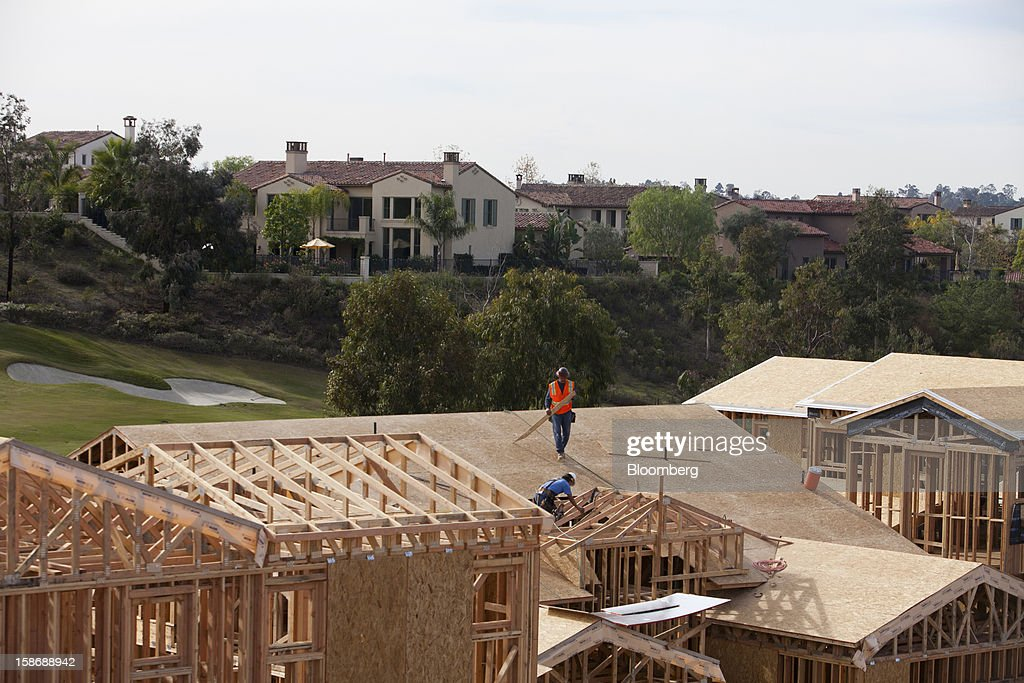 Workers install roofing material on a house under construction at Davidson Communities LLC's Arista at The Crosby development in Rancho Santa Fe, California, U.S., on Friday, Dec. 21, 2012. New home sales climbed to a 380,000 annual rate in November, the most since April 2010, according to the median forecast of 60 economists surveyed by Bloomberg before Dec. 27 figures from the Commerce Department. Photographer: Sam Hodgson/Bloomberg via Getty Images