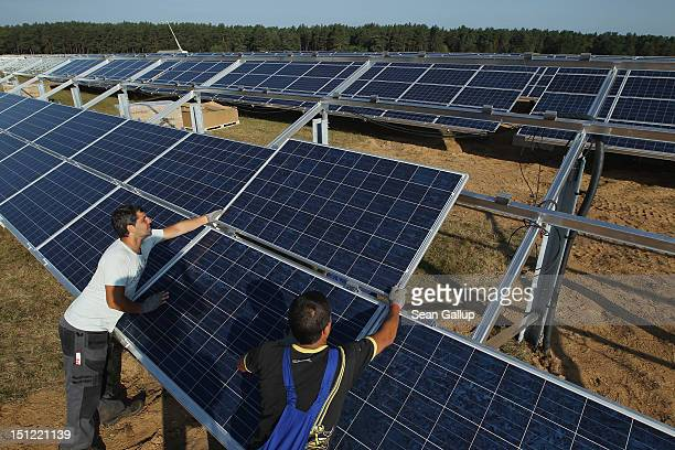 Workers install solar panels containing photovoltaic cells at the new Solarpark Eggersdorf solar park on September 4 2012 near Muencheberg Germany...