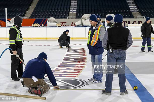 Workers install the lines and logos into the ice surface in advance of the 2016 Tim Hortons Heritage Classic on October 18 2016 at Investors Group...