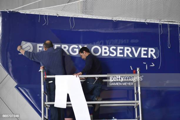 Workers install the logo of self energy producer multihull 'Energy Observer' on April 4 2017 in SaintMalo western France The Energy Observer an...
