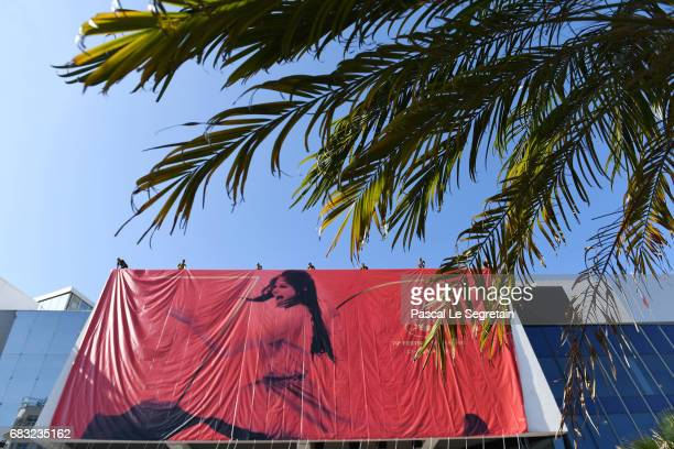 Workers install the official Poster of the 70th Cannes Film Festival at Palais des Festivals on May 15 2017 in Cannes France