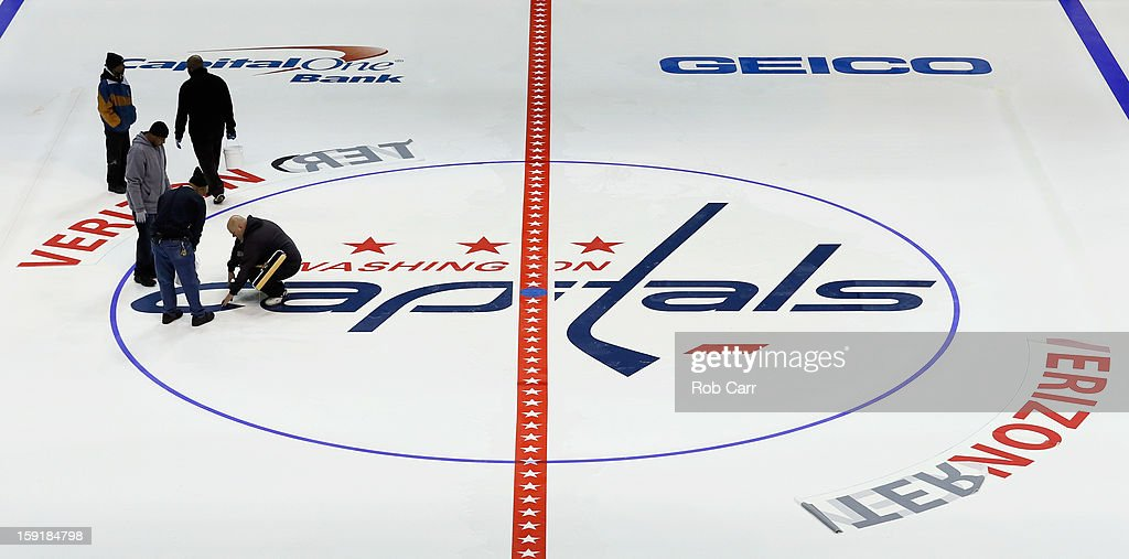 Workers install the Washington Capitals logo on the ice at Verizon Center on January 9, 2013 in Washington, DC.