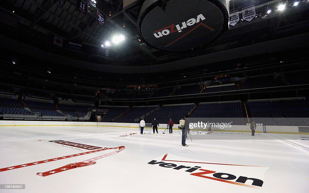 Workers install the Washington Capitals logo on the ice at Verizon Center on January 9, 2013 in Washington, DC.