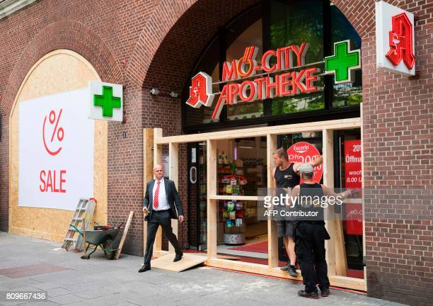 Workers install wooden panels on the windows of a pharmacy protect the shop against possible riot damages on July 6 2017 in Hamburg northern Germany...