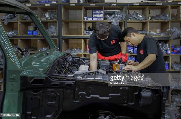 Workers installing engine part at mohenic garages in Paju South Korea A 20yearold beat up Hyundai SUV isn't anyone's idea of a dream car But used...