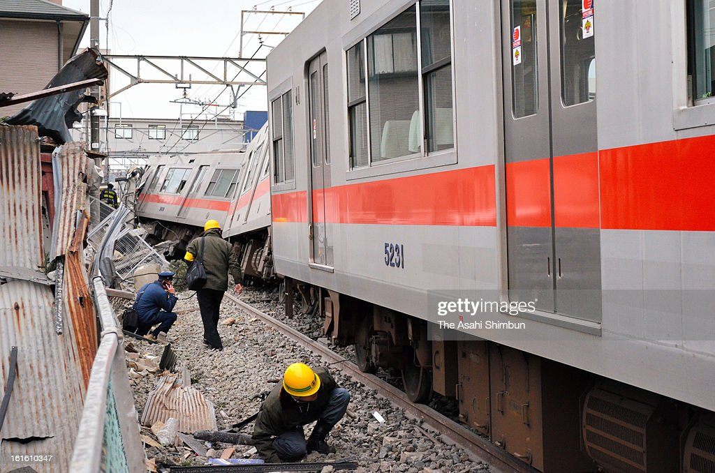 Workers investigate the derailed Sanyo Electric Railway Co. train is seen after a collision with a truck at Arai Station on February 12, 2013 in Takasago, Hyogo, Japan. Fifteen people injured by the accident.