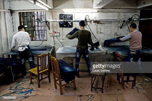 Workers iron newlymanufactured blue jeans in a little workshop by the street on February 10 2012 in Xintang Guangdong province ChinaThe town of...