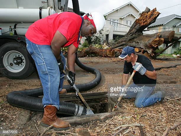 Workers Kevin James of Louisiana and Howard Hagedorn of Washington state both with PSC Industrial Outsourcing Inc clear storm drains near what...