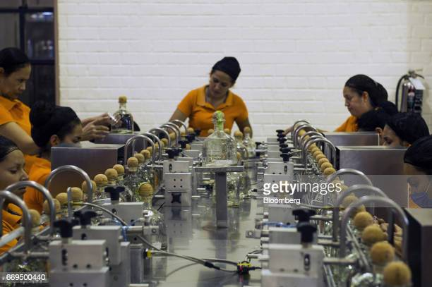Workers label bottles of Patron Spirits Co brand Silver Tequila at the company's distillery in Atotonilco El Alto Jalisco Mexico on Tuesday April 4...