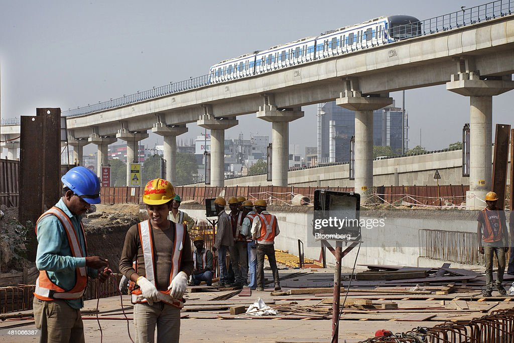 Workers labor at a construction site as a Rapid Metro train, operated by Rapid MetroRail Gurgaon Ltd., travels along an an elevated track, near DLF Cybercity in Gurgaon, India, on Wednesday, March 26, 2014. Indian stocks rose, sending the benchmark index to a record, after the rupee rose to an eight-month high and sovereign bonds gained on speculation the worlds largest democracy will elect a government capable of reviving economic growth. Photographer: Kuni Takahashi/Bloomberg via Getty Images