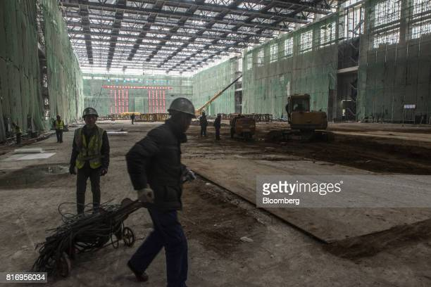 Workers labor at a film stage construction site inside the Dalian Wanda Group Co Oriental Movie Metropolis project site in Qingdao China on Saturday...