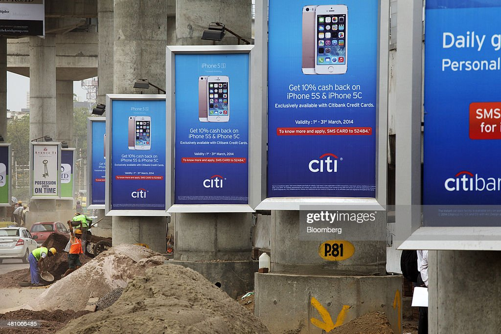 Workers labor at the roadside as Citigroup Inc. advertisements hang on concrete columns supporting an elevated track, operated by Rapid MetroRail Gurgaon Ltd., near DLF Cybercity in Gurgaon, India, on Wednesday, March 26, 2014. Indian stocks rose, sending the benchmark index to a record, after the rupee rose to an eight-month high and sovereign bonds gained on speculation the worlds largest democracy will elect a government capable of reviving economic growth. Photographer: Kuni Takahashi/Bloomberg via Getty Images