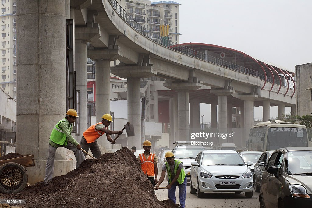 Workers labor at the roadside below an elevated track, operated by Rapid MetroRail Gurgaon Ltd., near DLF Cybercity in Gurgaon, India, on Wednesday, March 26, 2014. Indian stocks rose, sending the benchmark index to a record, after the rupee rose to an eight-month high and sovereign bonds gained on speculation the worlds largest democracy will elect a government capable of reviving economic growth. Photographer: Kuni Takahashi/Bloomberg via Getty Images
