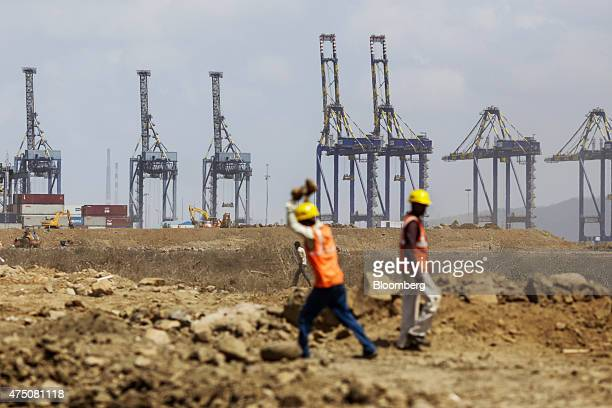 Workers labor in front of gantry cranes at Nhava Sheva Port in Navi Mumbai India on Monday May 25 2015 India's economy probably grew 74 percent in...