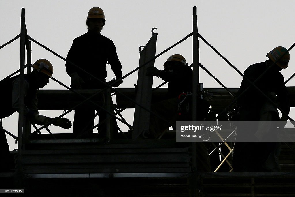 Workers labor on a construction site for a hospital in Tokyo, Japan, on Tuesday, Jan. 8, 2013. Prime Minister Shinzo Abe aims to compile Japan's economic stimulus package on Jan. 11, and seeks to have new economic growth strategy by mid-year. Photographer: Kiyoshi Ota/Bloomberg via Getty Images