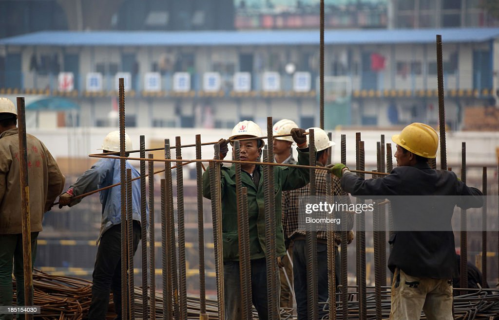 Workers labor on a construction site for a residential property in Wuhan, China, on Thursday, Oct. 17, 2013. China is scheduled to release third-quarter gross domestic product figures on Oct. 18. Photographer: Tomohiro Ohsumi/Bloomberg via Getty Images