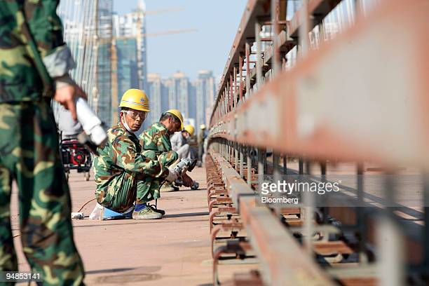 Workers labor on a soon to be completed bridge across the Pearl River in Guangzhou China on Thursday Nov 13 2008 China's central government will...