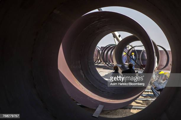 Workers labor on metal pipes at the coal mining site in Pakistan.