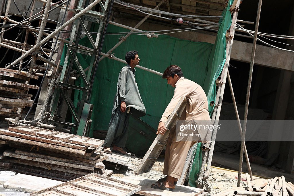 Workers labor on the construction site of a new apartment block in Karachi, Pakistan, on Wednesday, May 8, 2013. Pakistan is to hold parliamentary elections on May 11. According to opinion polls, Nawaz Sharif of the Pakistan Muslim League-N (PMLN) leads Imran Khan of Pakistan Tehrik-e-Insaf (PTI) in the race to replace president Asif Ali Zadari and become Pakistan's 12th president. Photographer: Asim Hafeez/Bloomberg via Getty Images