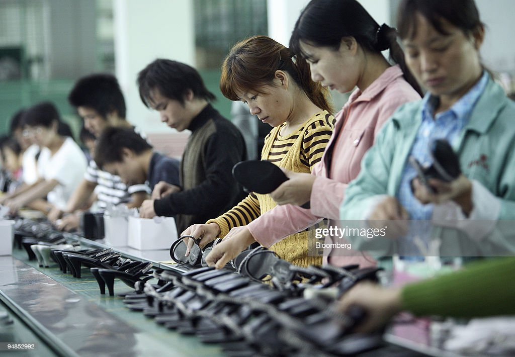Workers labor on the production line for women's shoes at the Junsheng Shoe factory in Dongguan China on Wednesday Nov 12 2008 China faces a...