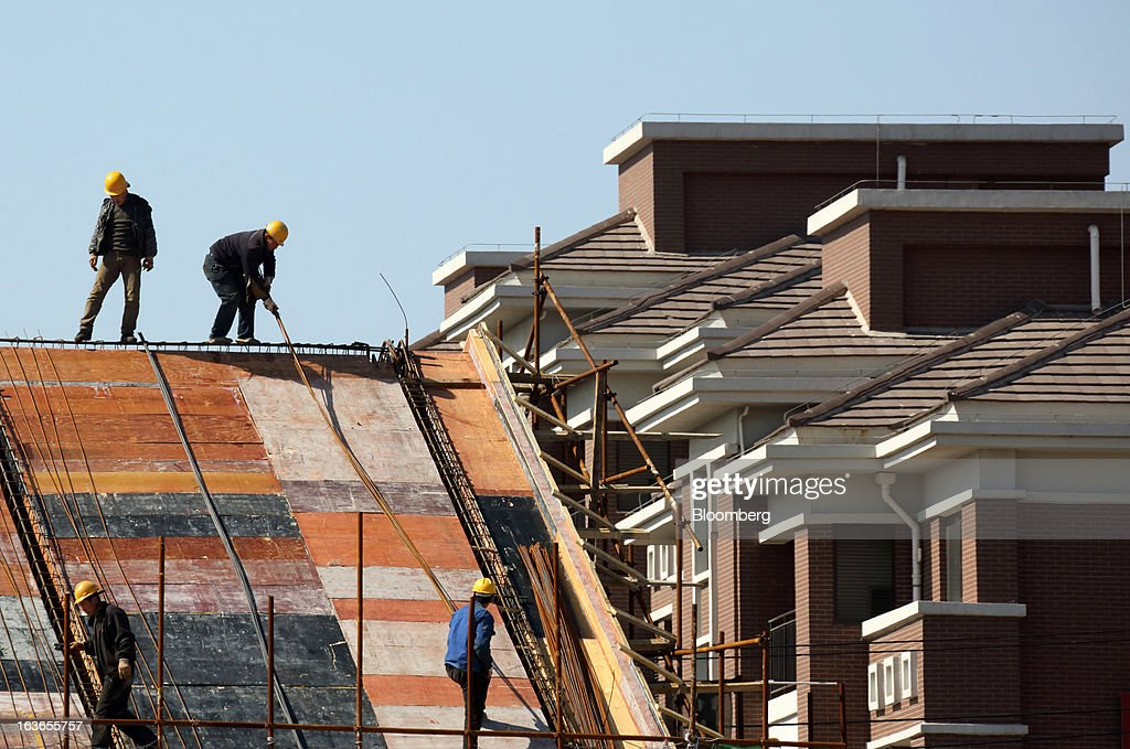 Workers labor on the roof of a house under construction next to residential apartments at the Sino-Singapore Tianjin Eco-city in Tianjin, China, on Wednesday, March 13, 2013. China's money-market rate rose to a one-week high after central bank Governor Zhou Xiaochuan said yesterday the nation should be on 'high alert' over inflation. Photographer: Tomohiro Ohsumi/Bloomberg via Getty Images