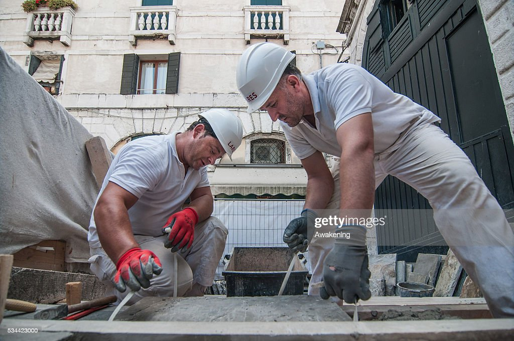 Workers lay a stone in the stairs during the renovation of the Rialto Bridge on May 26, 2016 in Venice, Italy. Site visits were organized to see the renovation of the Rialto bridge to coincide with the 15th Biennale of Architecture in Venice.