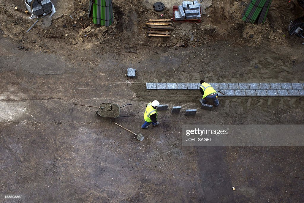 Workers lay and cement pavings on a construction site on December 18, 2012 in Paris.