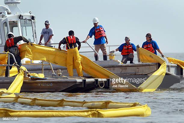 Workers lay down an oil boom as the effort continues to try and keep the massive oil spill in the Gulf of Mexico from washing ashore on May 3 2010 in...