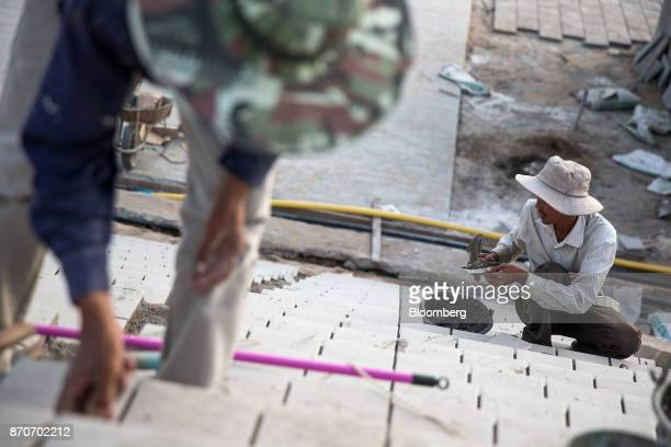 Workers lay floor tiles at a construction site in Vientiane Laos on Thursday Nov 2 2017 Located in the Mekong region Southeast Asia's frontier...