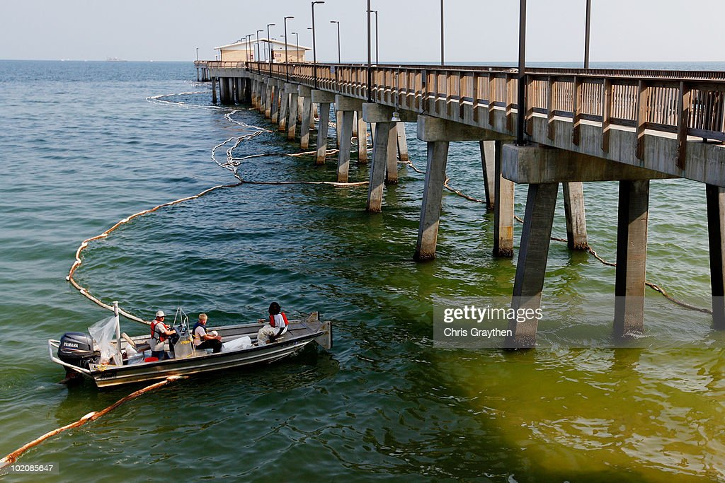 Workers lay out new lines of boom along a pier on June 14, 2010 in Gulf Shores, Alabama. U.S. government scientists have estimated that the flow rate of oil gushing out of the ruptured Deepwater Horizon oil well in Gulf of Mexico may be as high 40,000 barrels per day.