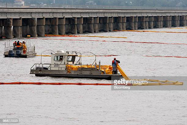 Workers lay out oil booms as part of containment efforts for the BP Plc Deepwater Horizon oil spill threatening the coast in Bay St Louis Mississippi...