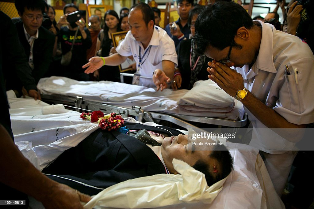Workers lay the body of Sutin Tharatin, a core anti-government leader who was killed by gunmen yesterday in Bangkok on January 27, 2014 in Bangkok, Thailand. Nine others were also injured during election related violence as protesters blocked polling stations as advanced voting took place in the capital city. Bangkok Shutdown has been in effect for two weeks as the anti-government protesters continue to block major intersections. The Thai government imposed a 60-day state of emergency in Bangkok and the surrounding provinces in an attempt to cope with the on-going political turmoil but so far this decree has had no effect on the mass protests.