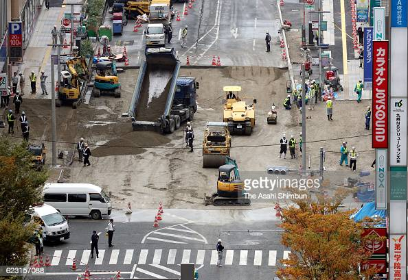 Workers level the sinkhole site to pave the road after the restoration work had been completed on November 14 2016 in Fukuoka Japan The sinkhole...