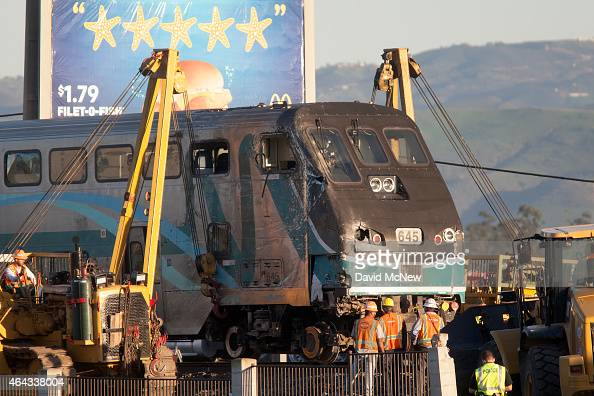 Workers lift a rail car back onto the tracks after a Los Angelesbound Metrolink train derailed in a fiery collision with a truck on the tracks on...