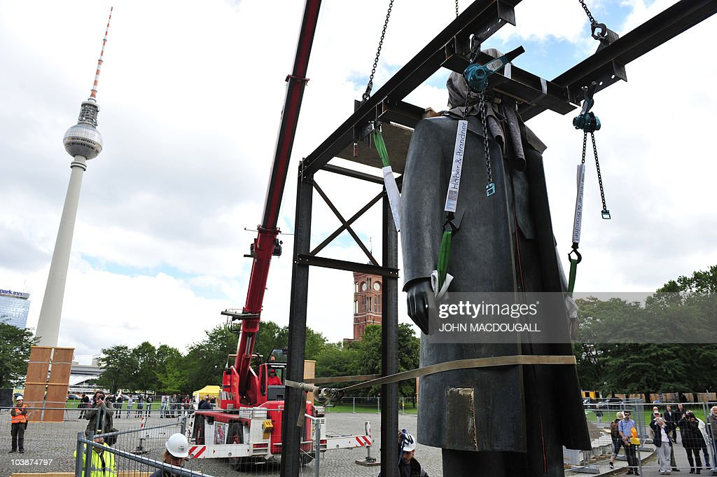 Workers lift a statue of German political philosopher Friedrich Engels off of its base separating it from a statue of Karl Marx, in Berlin on September 7, 2010. The two statues are being moved, one by one to allow for work on the new U55 underground line. They were made by east German sculptor Ludwig Engelhardt and inaugurated in 1986 by then Communist supremo Erich Honecker. Behind at (L) is seen landmark TV tower. AFP PHOTO / JOHN MACDOUGALL