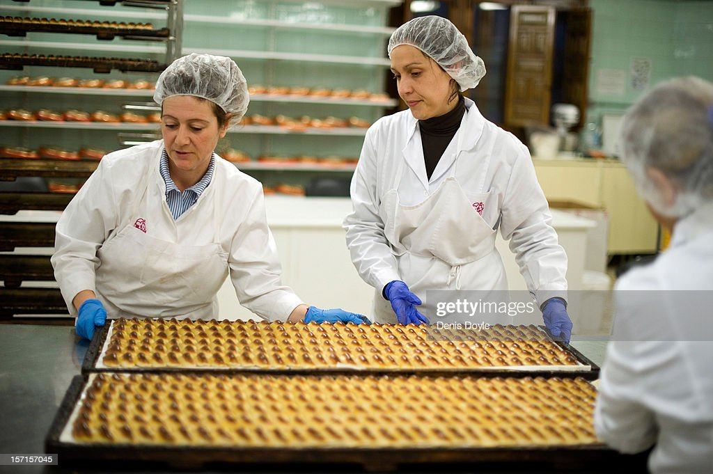 Workers lift a tray of almond pastry 'empenadas' at the Santo Tome Obrador de Mazapan cake bakery on November 29, 2012 in Toledo, Spain. The company, which employs 45 staff throughout the year, has hired an extra 25 workers leading up to the christmas festivities hoping comsumption picks up over the holiday period.
