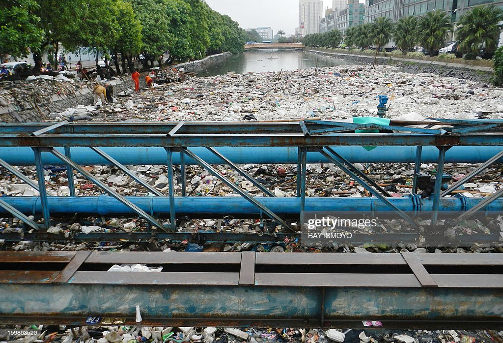 Workers lift garbage from the river in Jakarta on January 22, 2013 after being washed in by floodwaters. The death toll from floods in Indonesia's capital Jakarta had risen to 20 on January 21, according to National Disaster Mitigation Agency (BNPB), and the floods had forced 33,502 people from their homes. AFP PHOTO / Bay ISMOYO