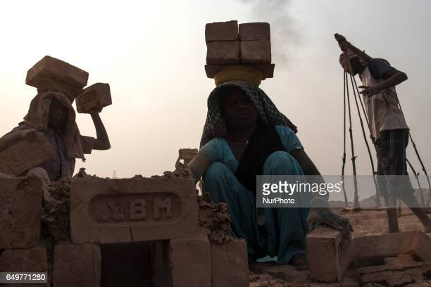 Workers lifting heavy loads in the Kamduni brick kiln Kamduni West Bengal India 080317 The brick kilns of Bengal employ a large number of laborers...