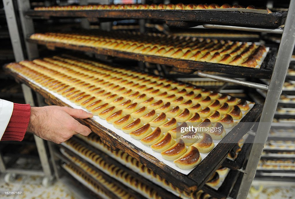 A workers lifts a tray of almond pastry 'empenadas' at the Santo Tome Obrador de Mazapan cake bakery on November 29, 2012 in Toledo, Spain. The company, which employs 45 staff throughout the year, has hired an extra 25 workers leading up to the christmas festivities hoping comsumption picks up over the holiday period.