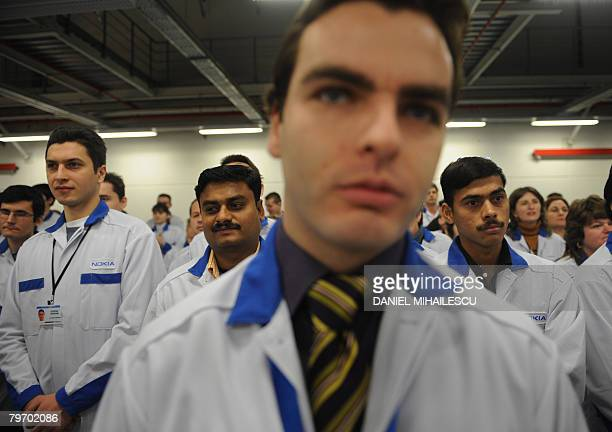 Workers listen to an inaugural speech at the Finnish cellphone maker Nokia factory in the Romanian village Jucu 500 kms northwest of Bucharest on...