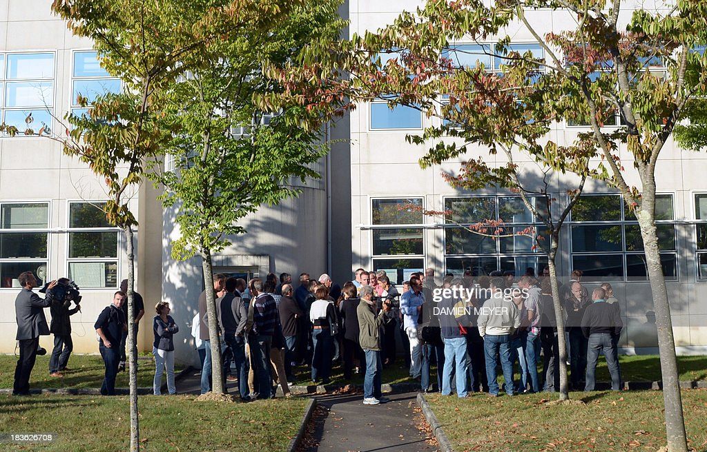 Workers listen to their delegates, on October 8, 2013 in Rennes, western France, in front of the plant of French-US telecom-equipment maker Alcatel-Lucent, after the group announced the cut of 10,000 jobs worldwide to reduce fixed costs by 15 percent in two years, the company announced on October 8, 2013. The company said that 4,100 jobs would be cut in Europe, the Middle East and Africa by 2015, 3,800 in the Asia Pacific region, and 2,100 in North and South America.
