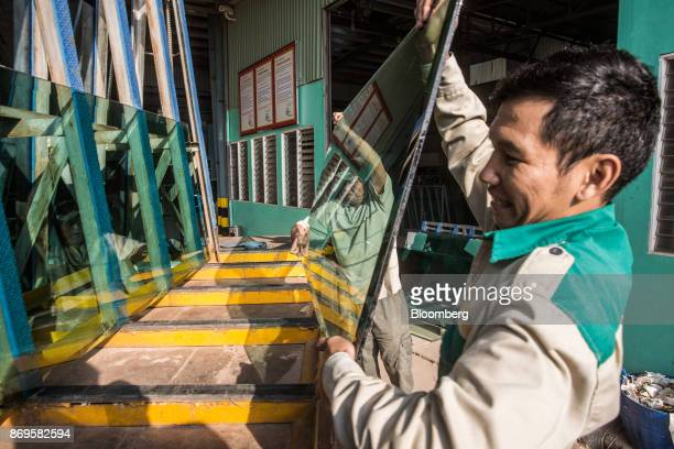 Workers load a sheet of glass onto a truck at the Somvang Glass Factory on the outskirts of Vientiane Laos on Wednesday Nov 1 2017 Asia'ssmallest...