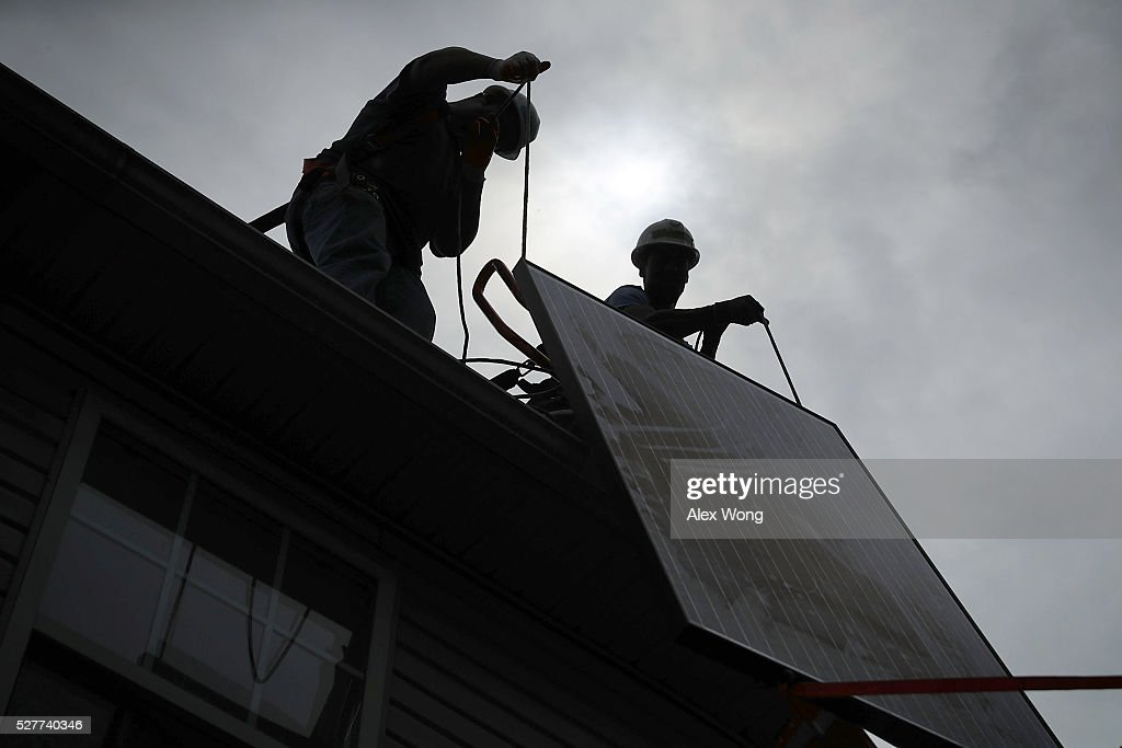 Workers load a solar panel up to the roof of a house for an installation May 3, 2106 in Washington, DC. The installation marked the one millionth in the U.S. in the past 40 years. It has been predicted that the U.S. will reach 2 million installations in two years.