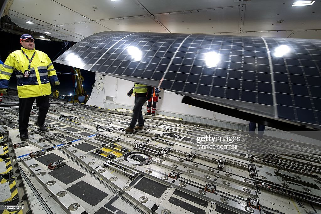 Workers load a wing of the Swiss sun-powered aircraft Solar Impulse into a Cargolux Boeing 747 cargo aircraft on February 20, 2013 at Payerne airport. The Boeing will carry Solar Impulse HB-SIA prototype aircraft to San Francisco for a serie of flights across America from the West to East Coast.