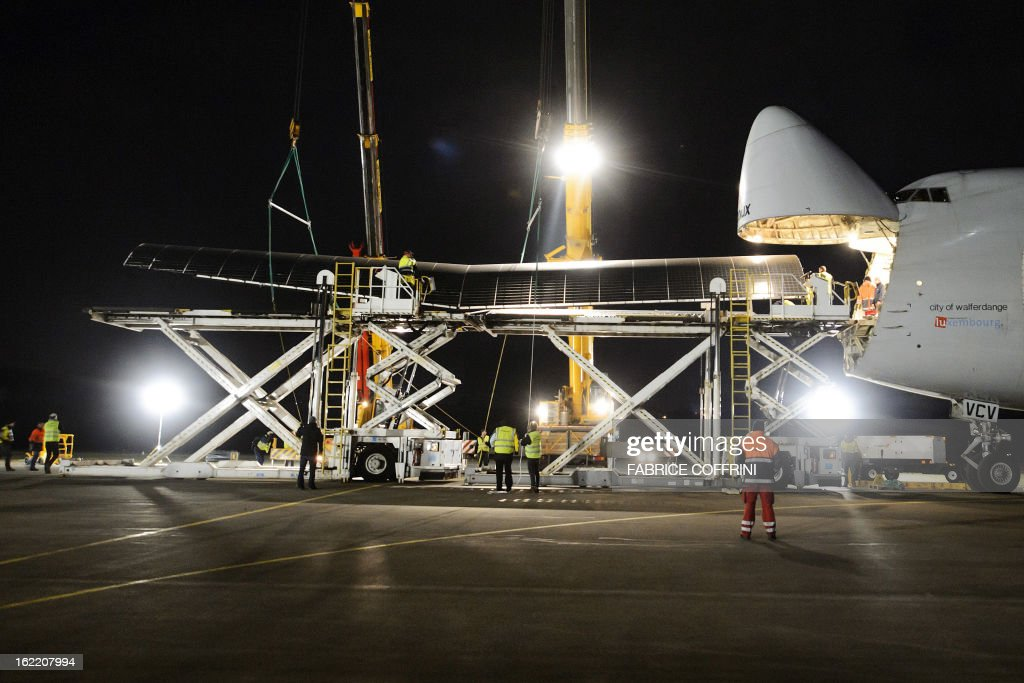 Workers load a wing of the Swiss sun-powered aircraft Solar Impulse into a Cargolux Boeing 747 cargo aircraft on February 20, 2013 at Payerne airport in Geneva. The Boeing will carry the Solar Impulse HB-SIA prototype aircraft to San Francisco for a series of flights across the US from the West to East Coast.