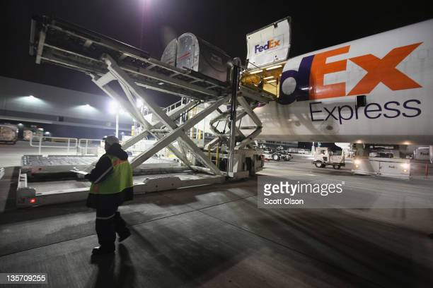 Workers load an aircraft at a FedEx shipping facility at O'Hare Airport on December 12 2011 in Chicago Illinois With an anticipated 17 million...