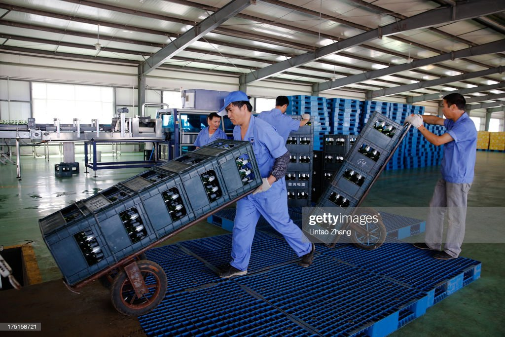 Workers load beer onto a truck at the Jinzhu Manjiang beer factory on August 1, 2013 in Fujin, Heilongjiang Province, China. Recent significant sustained high temperatures in China are expected to push beer industry volume and revenue growth up significantly.